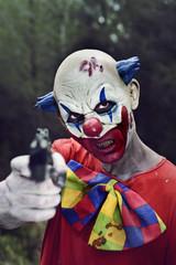 scary evil clown with a gun
