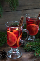 Two glasses cup of delicious Christmas hot mulled wine with oranges and spices on wooden background