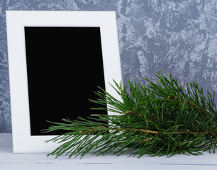Blank photo frame behind christmas trees branch