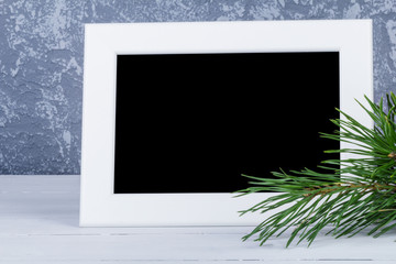 Photo frame behind christmas trees branch