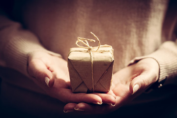 Giving a gift, handmade present wrapped in paper