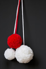 rot und weiße Pompons vor scharzem Hintergrund