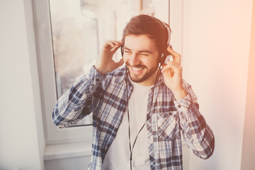 man with headphones smiling and listening to music