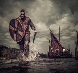 Viking warrior in attack, running along the shore with Drakkar on background