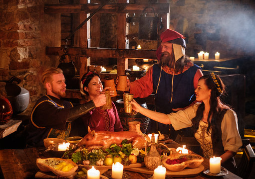 Medieval people eat and drink in ancient castle kitchen interior