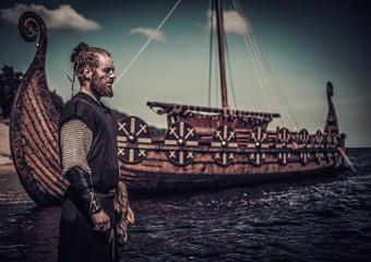 Viking warrior standing near Drakkar on seashore