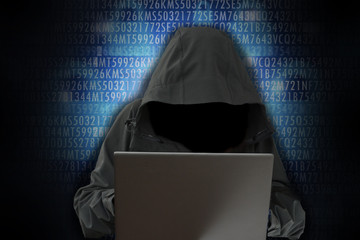 Unrecognizable hacker in front of computer – cybercrime concept
