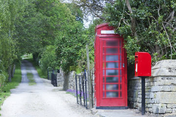 Fotorolgordijn Rood, zwart, wit Traditional English red telephone and post box by a dirty road in a rural village