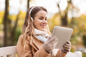 woman with tablet pc and headphones in autumn park