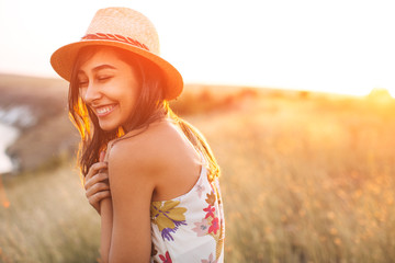 Lovely girl in stylish hat and summer dress smiling