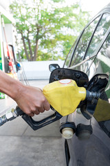 Pumping gas at gas pump. Closeup of man pumping gasoline fuel in