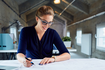 Beautiful businesswoman working with blueprints in industrial of