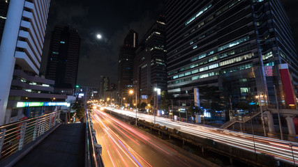 Night Bangkok street. Illuminated trails of intense transport traffic on the road with highrise buildings alongside. The moon in dark sky