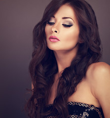 Beautiful chic female makeup model posing with long curly volume