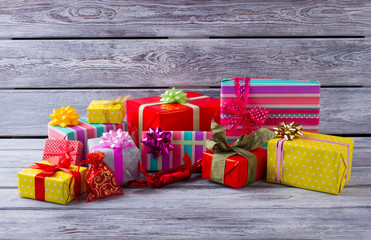 Heap of beautiful Christmas gifts on gray wooden background.