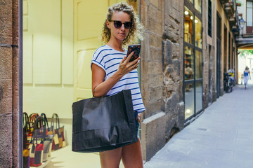 Girl,dressed in T-shirt and shorts,standing on street near glass case while looking at screen of smartphone, is in her hand.Woman holding black shopping bag with purchases.Girl is shopping.