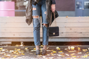 fall fashion outfit details. fashion blogger wearing ripped jeans with loafers, oversized bomber jacket and a trendy black bag.