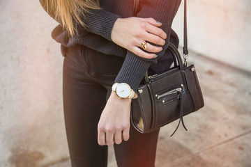 close up fashion details, young business woman holding her bag. wearing golden jewelry, and watch.