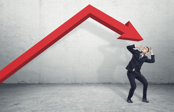 Businessman standing in desparate pose under the giant red arrow aiming down at him
