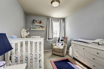 Baby bedroom interior. Gray walls and white wooden furniture