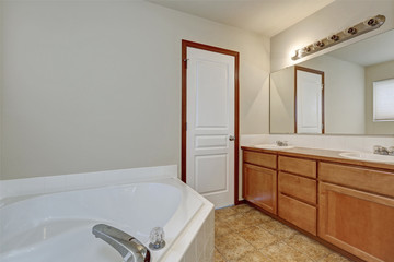 White bathroom interior with corner bathtub and vanity cabinet.
