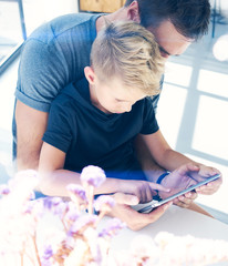 Happy father with young son using tablet PC in sunny room.Dad and little boy playing computer resting indoor together.Vertical, blurred background.