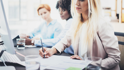 Beautiful blonde woman signing documnet on workplace in office. Group of girls coworkers discussing together business project. Horizontal, blurred background.