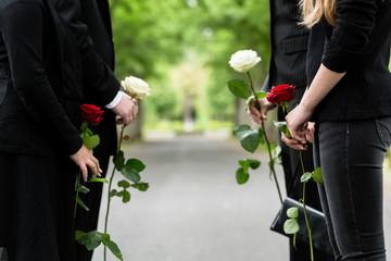 Familie erweist Verstorbenen letzte Ehre und steht im Spalier auf Friedhof bei Beerdigung