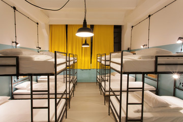 Interior design of a dorm room of tourist hostel with clean beds for twelve people