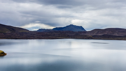 Lake with small island and sky reflection at cloudy day in Iceland