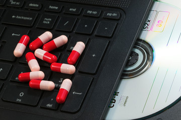 Antibiotics capsule on  infected laptop with CD rom