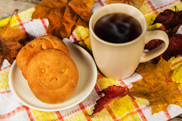 Hot drink, biscuits with a smile and autumn leaves