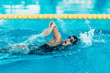 Swimmer on training . Female swimming  front crawl  in the indoor pool