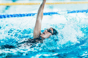 Back stroke swimmer. Female swimmer in the swimming pool