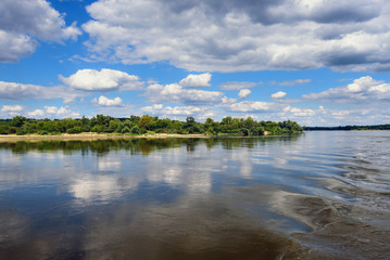 Vistula river in sunny summer day with reflections of clouds and blue sky. Poland, Europe.