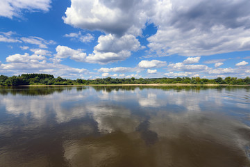 Picturesque clouds on the blue sky over Vistula river in sunny day. Poland, Europe.