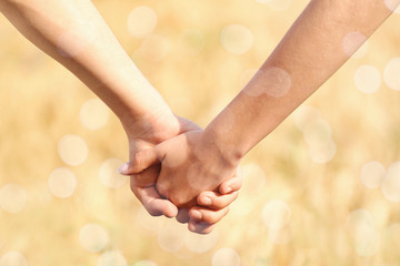 Young couple holding hands together on blurred field background