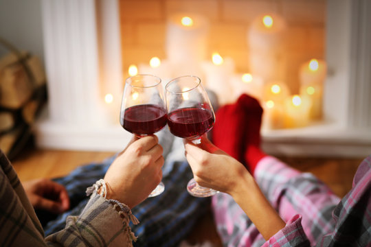 Couple drinking wine in front of fireplace at home