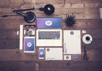 Laptop, Tablet, Smartphone, and Stationery on Dark Wooden Desk