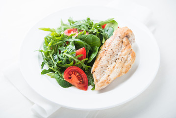 Roasted chicken breast and fresh salad with tomato and greens (spinach, arugula) close up on white wooden background. Healthy food.
