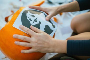 Boy making Halloween pumpkin outdoors.