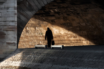 Silhouette of man walking along the Seine river