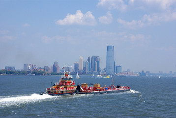 Tugboat pushing barge in New York Harbor