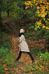 A pretty young blonde woman in a stylish coat and scarf posing on a footpath in autumn forest