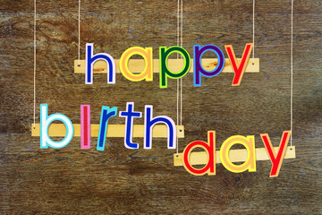 Happy Birthday. Bright multi colored painted letters over dark wooden background