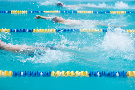 Junior competitive swimming with events in backstroke style. Boys are swimming in a race. Focus on water splash, some motion blur.