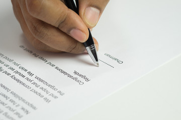 Hand signing a letter on congratulation document