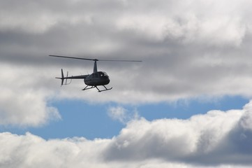 Flying helicopter in the cloudy sky