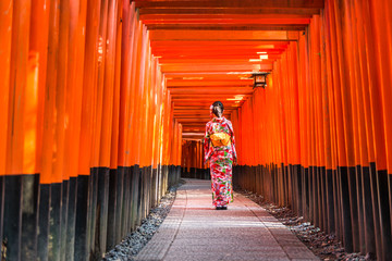 Women in kimono stand at Red Torii gates in Fushimi Inari shrine, one of famous landmarks in Kyoto, Japan Wall mural