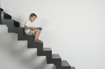 Germany, Boy (4-5 years) sitting on stairs and reading book